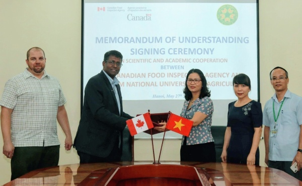 Prof. Dr. Nguyen Thi Lan and Dr. Aruna Ambagala exchange the Memorandum of Understanding