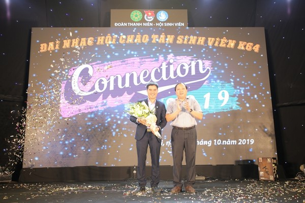 Dr. Phạm Quý Giang, President of University Student Union, receives flowers from Dr. Vu Ngoc Huyen, Permanent Deputy Secretary of the Party Committee